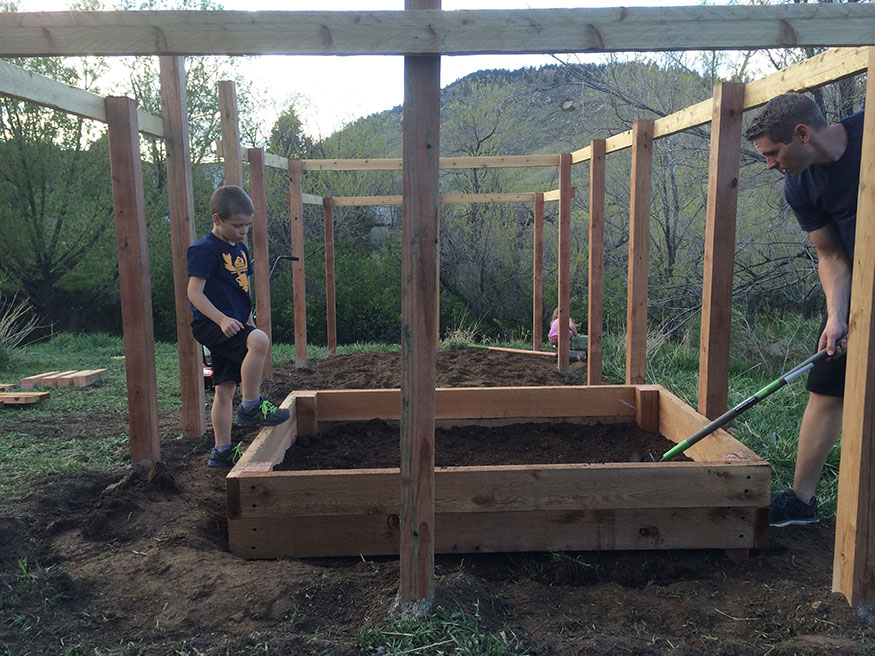 Adding compost for raised garden.